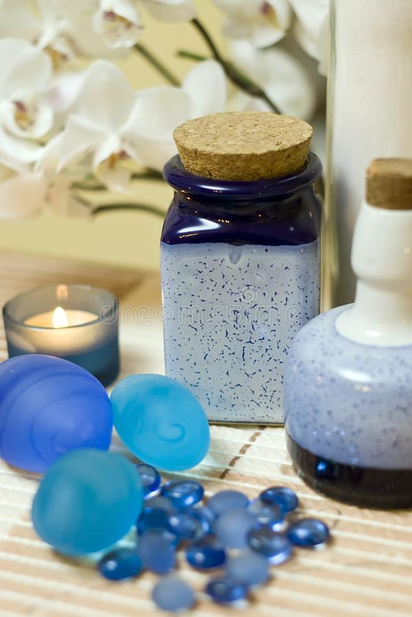 Blue vases composition. A decorative composition of blue vases and glass pebbles, orchid flower in the background royalty free stock images