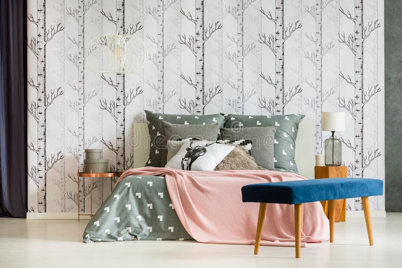 Blue velvet bench. Standing next to a bed with patterned bedclothes, pink blanket and deer cushion stock images