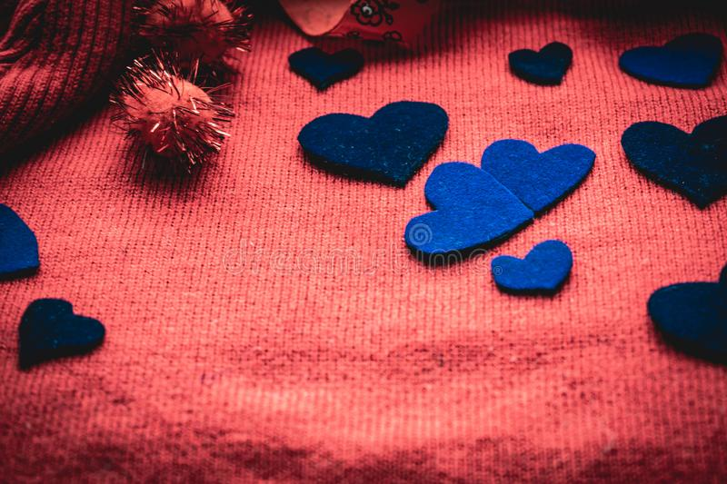 Blue velvet hearts on a red fabric background, with gift boxes for Valentine`s day. Valentine`s day in soft colors. A festive roma stock photography