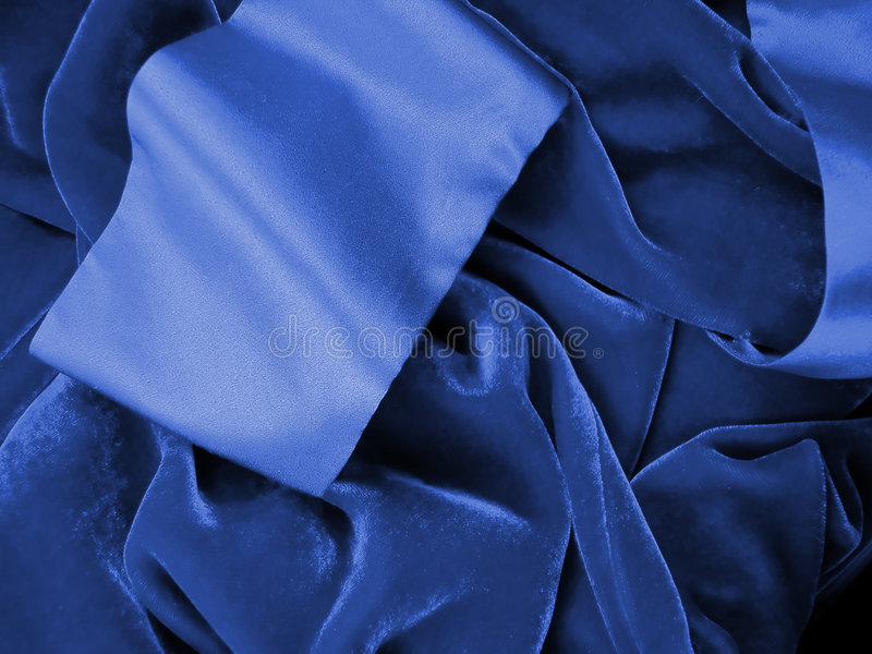 Blue Velvet Robe. Background shot of a blue velvet robe with silky cuffs in a pile stock photo
