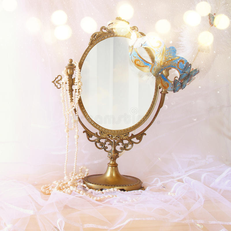 blue venetian mask next to old vintage oval mirror stock photography