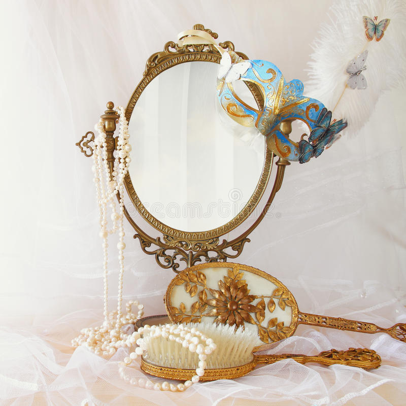 blue venetian mask next to old vintage oval mirror stock photo
