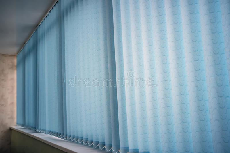 Blue vertical blinds on the long window on balcony. Modern interior design. Closed window from sunlight. Blue vertical blinds on the long window on the balcony stock images
