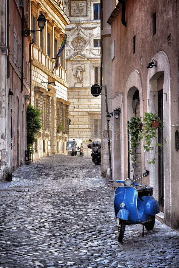 Blue Vespa in the old street of Rome royalty free stock images