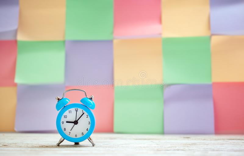 Blue vintage alarm clock on a colorful timetable background.  royalty free stock image