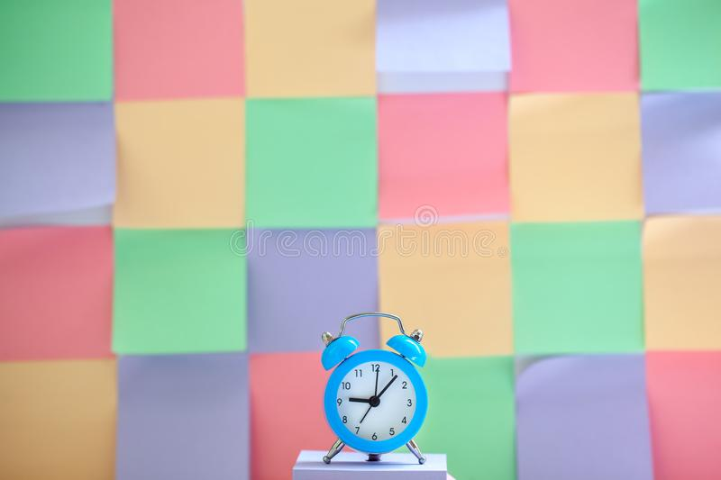 Blue vintage alarm clock on a colorful timetable background.  stock photography