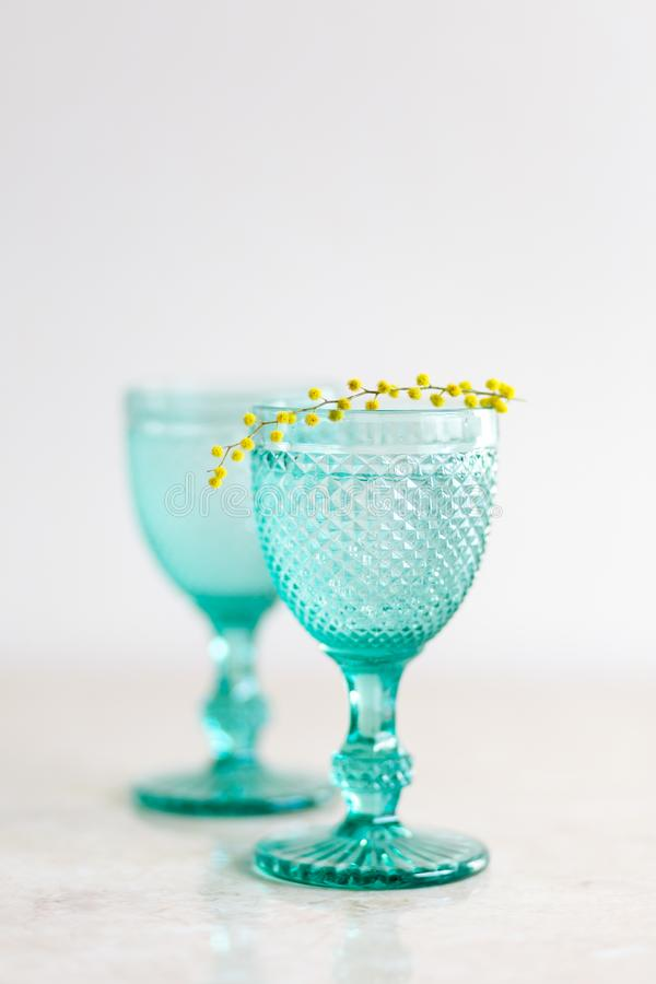 Blue Vintage Goblets and yellow mimosa flowers. Wineglasses on whight background stock photo
