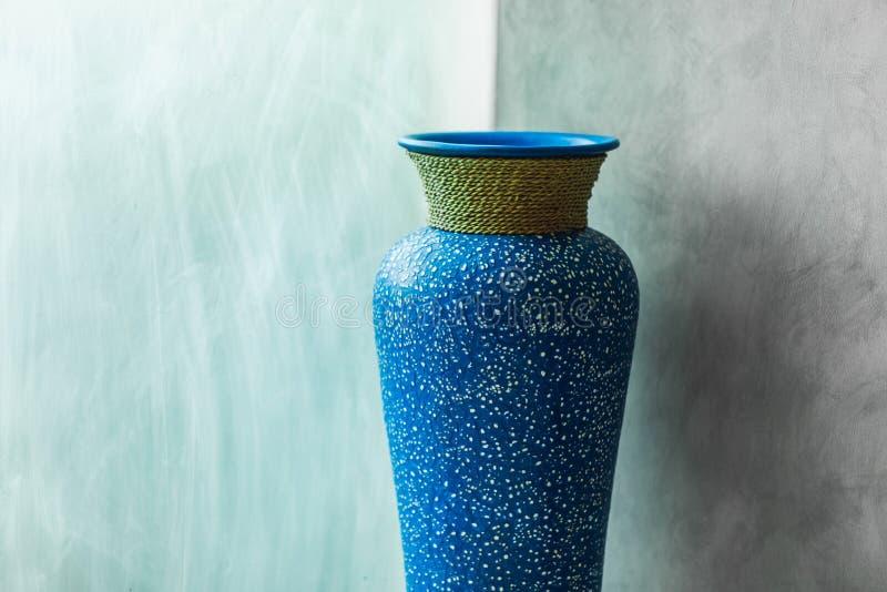 Blue vintage vase on gray concrete wall background. Minimalist modern interior design royalty free stock image