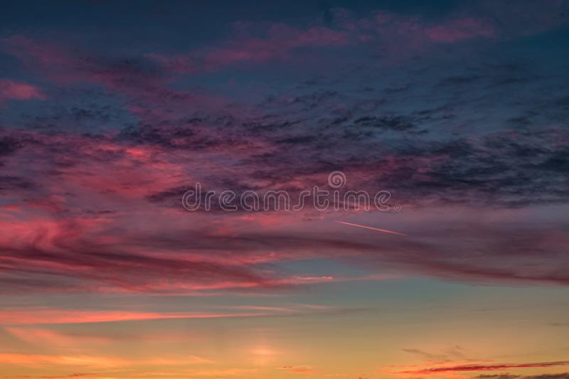 Blue violet red sunset sky background with evening fluffy curly rolling cirrostratus clouds. Good windy weather royalty free stock photo