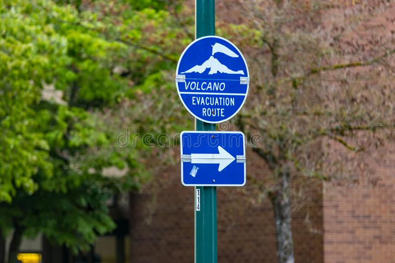 Blue volcano evacuation route sign and arrow. On a green post stock images