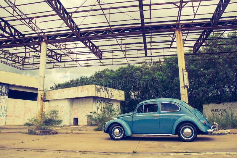 Blue Volkswagen Beetle in Front of Building stock photography