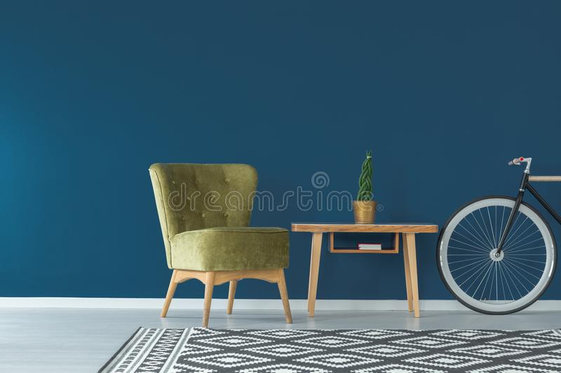 Blue wall and coffee table. Sophisticated interior with blue wall, wooden coffee table, bike, patterned rug and vintage armchair in olive green color stock images