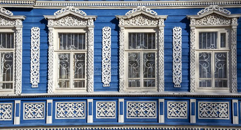 The blue wall of the house with Windows and beautiful carved wooden frames. The blue wall of the house with Windows and beautiful carved wooden frames royalty free stock photography