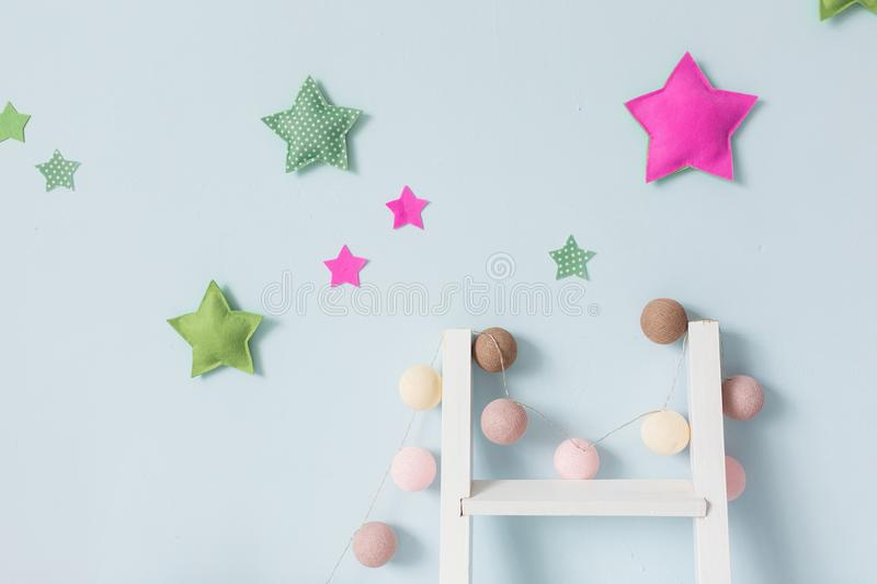 Blue wall with textile stars and ball garland decor. Horizontal shot for banner.  royalty free stock image