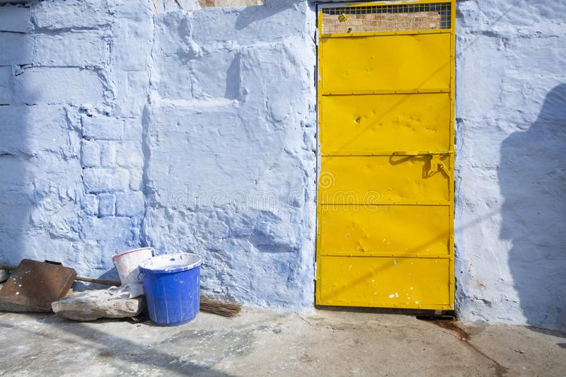 Blue wall with yellow door of house. In Jodhpur city, Rajasthan State, India stock images