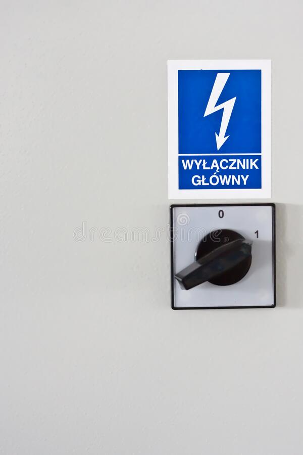 Blue warning sign with lightning and inscription plate  `main switch` on the electrical cabinet in Polish language. stock photos