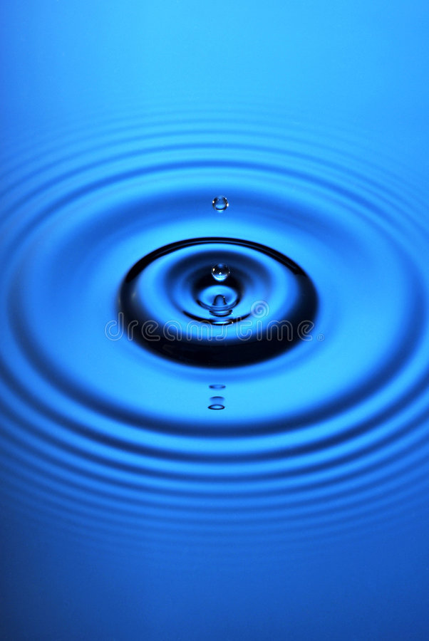 Blue Water Drop Ripple. Water dropping on to a blue water surface stock photo