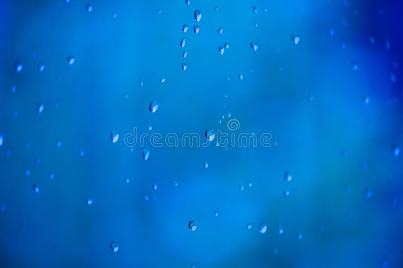 Blue water drops on a window stock images
