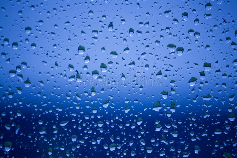 Blue water drops on a window royalty free stock photography