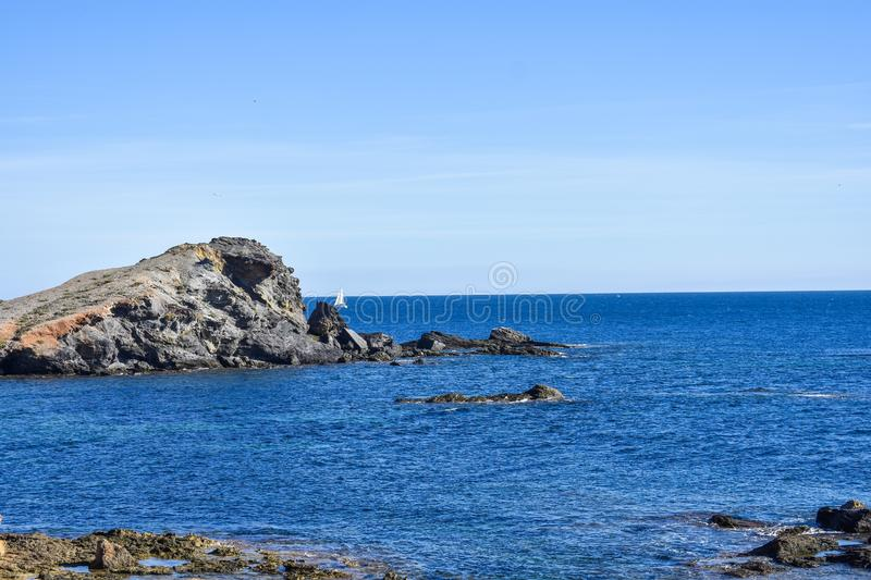 Blue water envelop a dark grey islet. Blue water envelop a dark grey rock or islet, that just rise above the surface along the southern coast of Spain royalty free stock images
