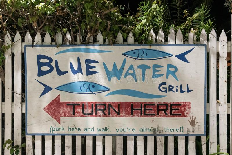 `Blue Water Grill` sign on the white fence in San Pedro, Belize. stock photography