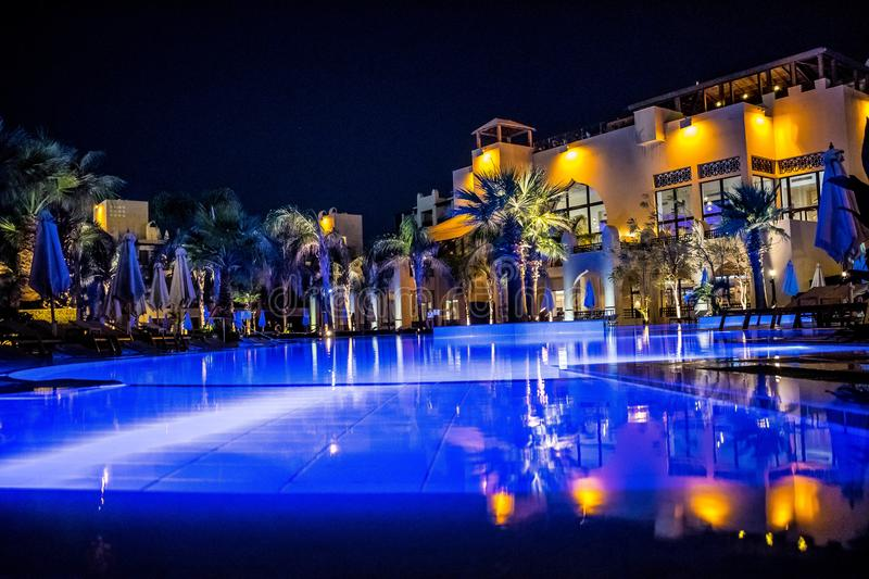 Blue water pool. Reflection of lantern light at night. Steigenberger Aqua Magic hotel in Hurghada, Egypt royalty free stock images