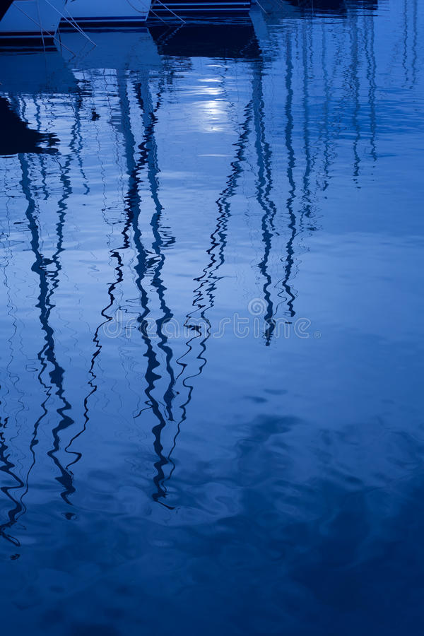 Blue water reflection of sailboats boats poles in waves stock image