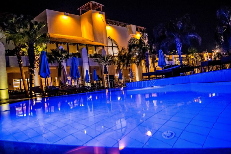 Blue water of swimming pool at night. Main building of the five star Steigenberger Aqua Magic hotel. Hurghada, Egypt stock photos