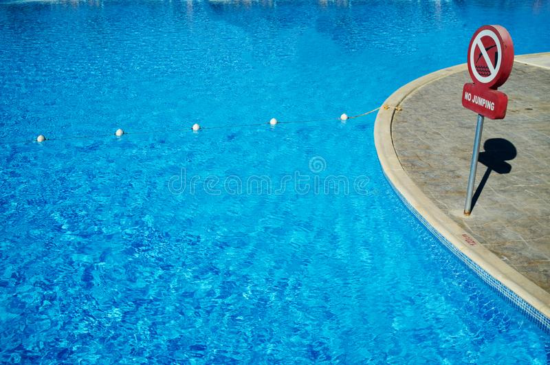 Blue water in the swimming pool, safety buoys. No jumping sign, texture, pattern, reflection, underwater, aqua, background, bright, clear, light, pure, shiny stock photos