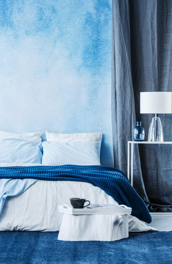 Blue watercolor paint on the wall in modern bedroom interior wit. H a double bed and grey curtain royalty free stock photo