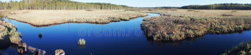 Blue waterway panorama. Panoramic view of blue, marshy waterway in daylight royalty free stock photo