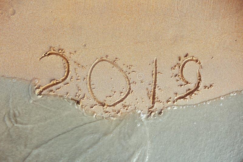 Blue Wave Washing Away 2019 Year Handwritten On Sandy Beach inscription royalty free stock photos