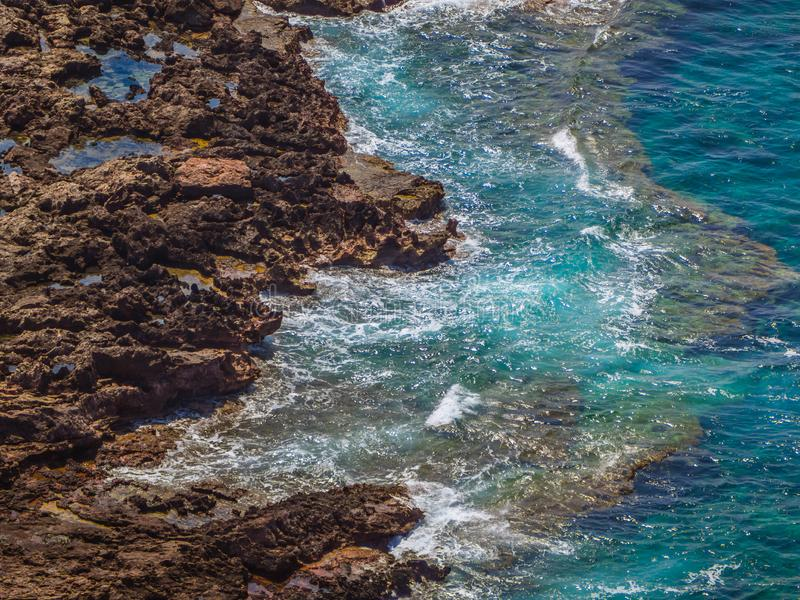 Blue waves and jagged rock shore stock photo