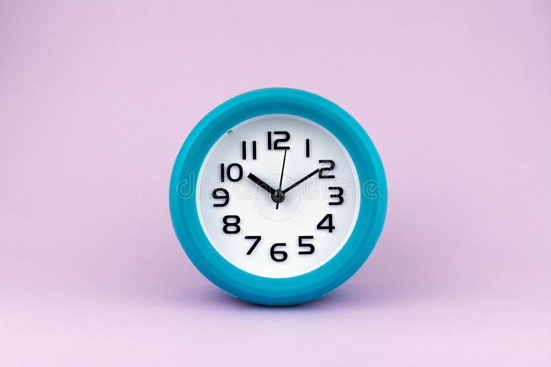 Blue and white alarm clock on pink background.  stock images