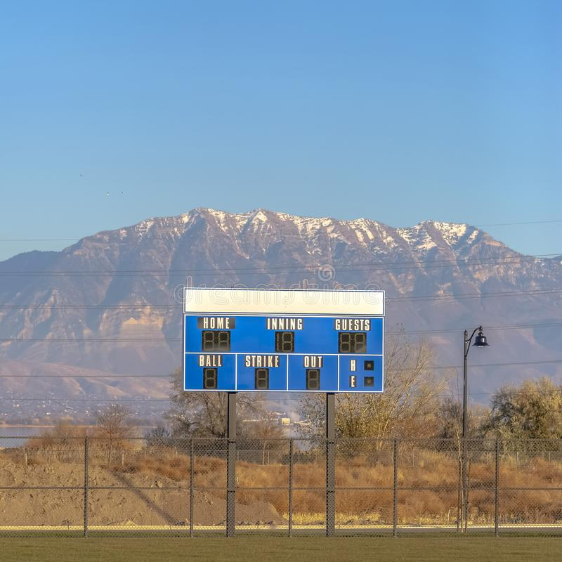 Blue and white baseball scoreboard above the chain link fence at a sports field. A lake and snow capped mountain under blue sky can be seen in the background stock photography