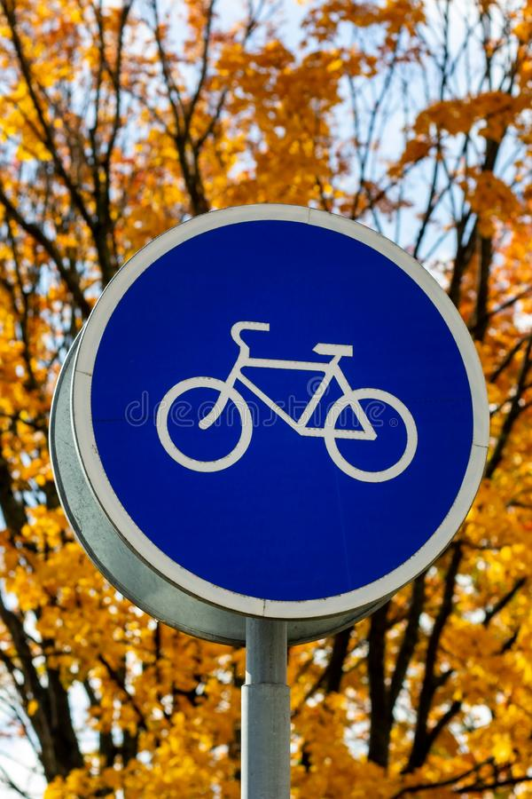 Blue and white bicycle lane sign indicating bike route, large round roadside traffic signage. stock images