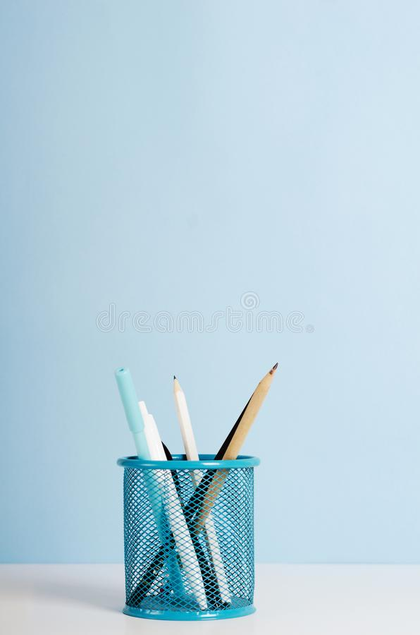 Blue, white and black pencils, pens in a stand on a white table on a blue background, office desk. Copy space.  royalty free stock photography