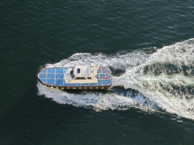 Blue and white boat plows the surface of the blue sea, leaving a foam trail. The view from the top stock photography