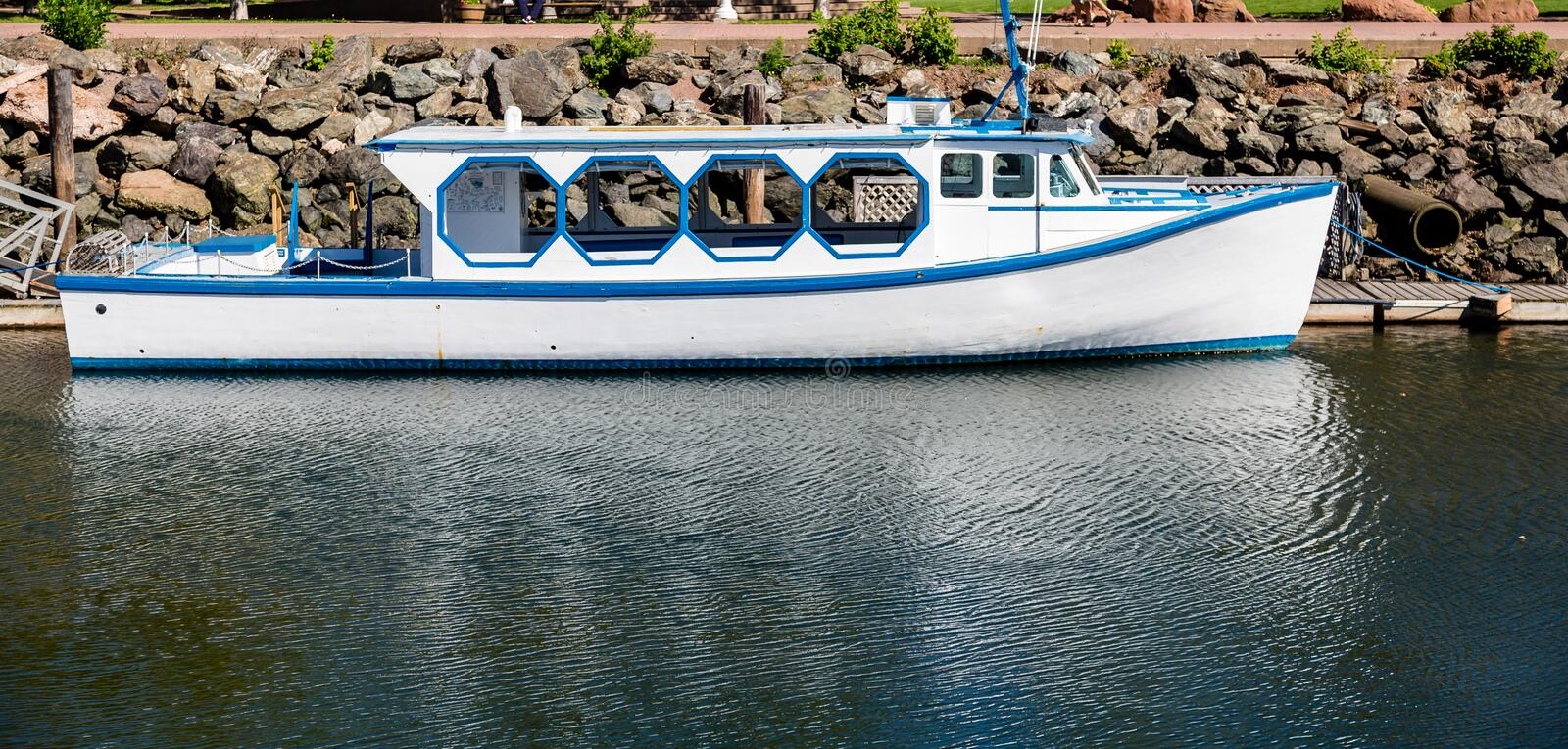 Blue and White Boat by Seawall. Fishing boats in harbor of Charlottetown, Prince Edward Island royalty free stock photos