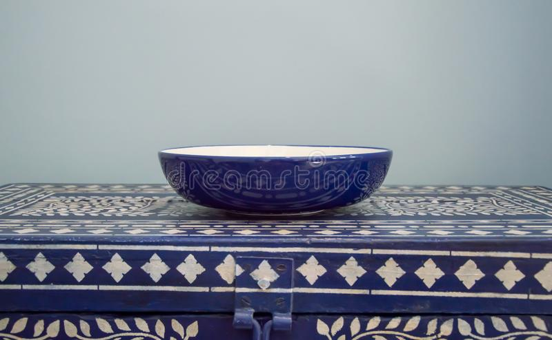 Blue and white bowl on table. Blue and white bowl on a blue and white chest with reflections stock photos