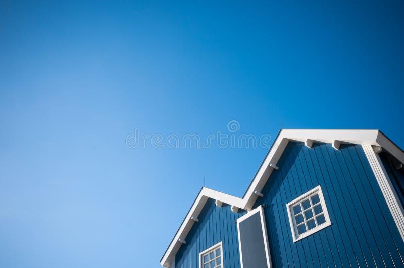 Blue and white building facade. Facade of a wooden, blue and white building facade against a cloudless blue sky royalty free stock photo