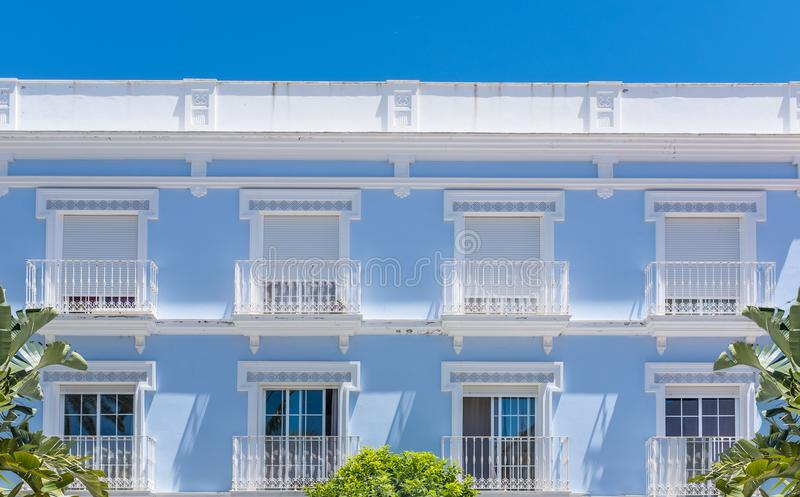 Blue and white building with shutters and balconies in Southern. The facade of an elegant blue and white building against a blue sky. There are shutters on the royalty free stock photo