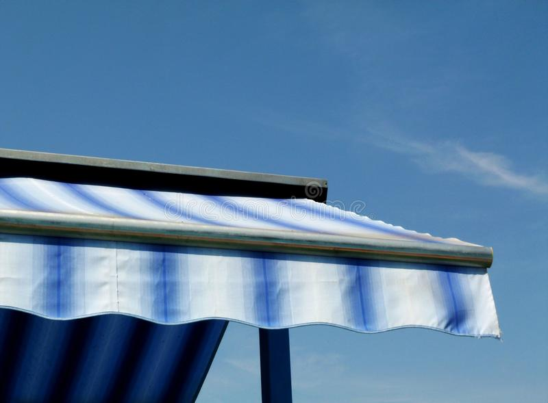 Blue and white canvas awning under blue sky. Blue and white striped canvas awning sun shade on aluminum frame under blue sky with white clouds royalty free stock image