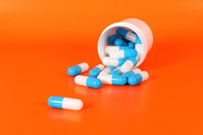 Blue and white capsules with a white tin. Blue and white capsules are lying in a plastic tin in the orange studio royalty free stock image
