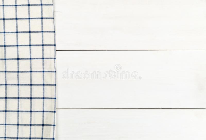 Blue and white checkered dishcloth on white wooden plank table flat lay top view from above stock photography