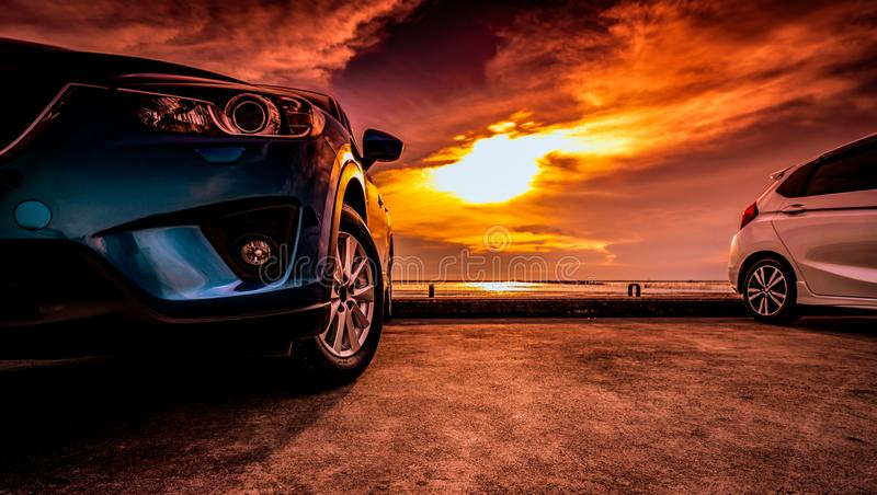 Blue and white compact SUV car with sport and modern design parked on concrete road by the sea near the beach at sunset. stock photos