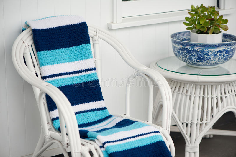 Blue and white crochet throw. Handmade blue and white crochet throw on white cane outdoor furniture royalty free stock image