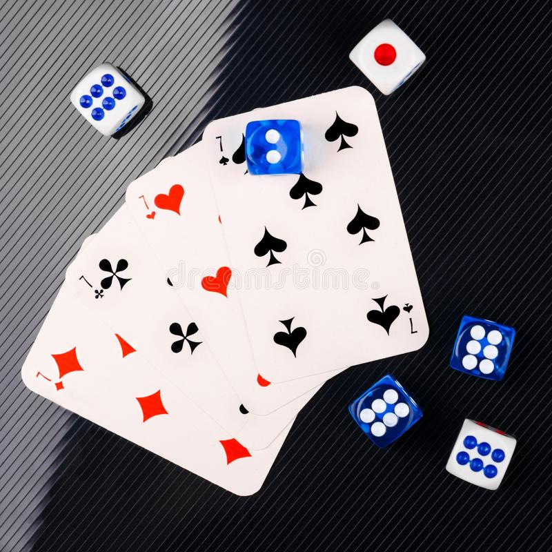 Blue and white dices and cards on black glossy background. flat lay. Several blue and white dices and cards on black textured background. Closeup stock images