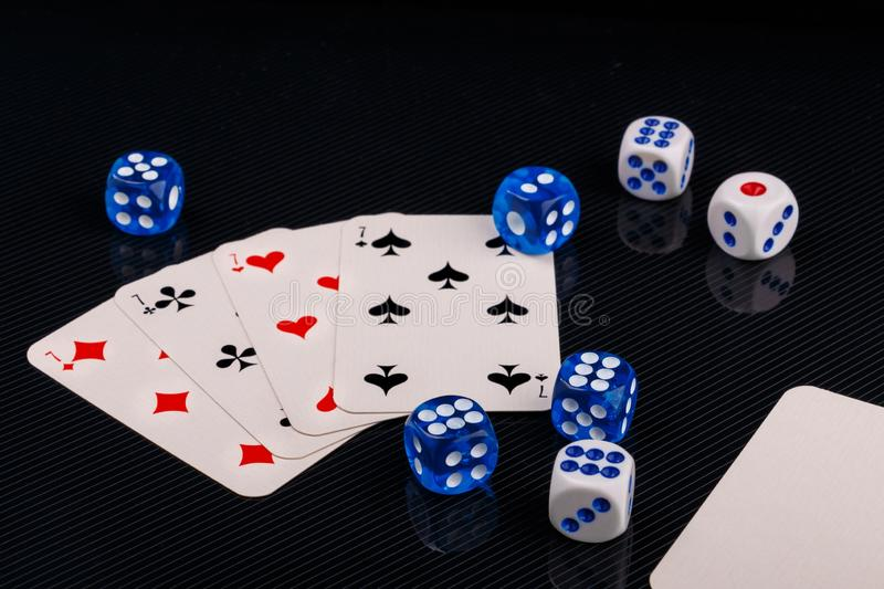 Blue and white dices and cards on black glossy background. Several blue and white dices and cards on black textured background. Closeup stock photos