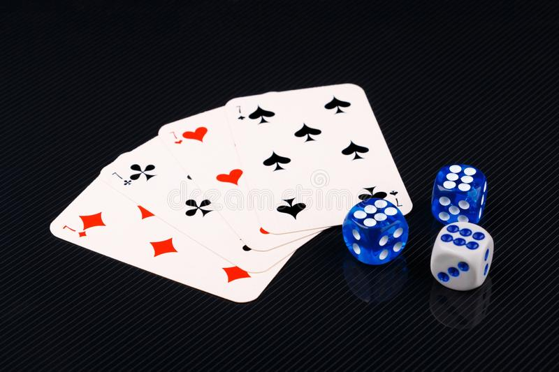Blue and white dices and cards on black glossy background. Several blue and white dices and cards on black textured background. Closeup royalty free stock images